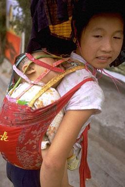 Китаянка несет ребенка в традиционной перевязи, «май-тее»